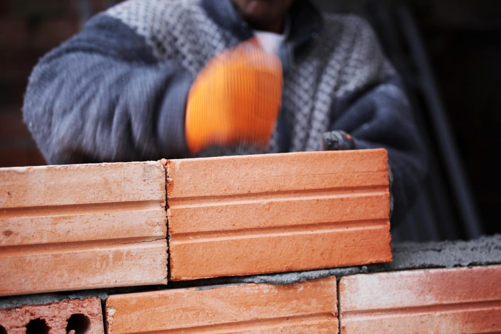 man pushing the brick to stick and flatten into the cement
