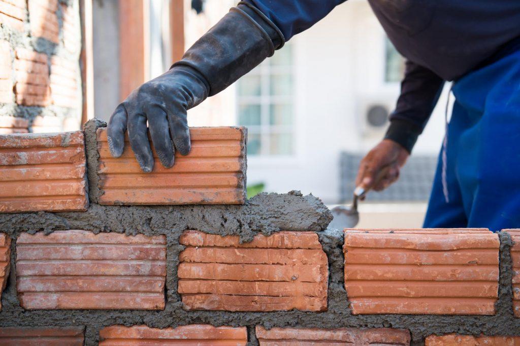 man applying cement and bricks